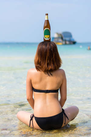 Sexy Asian Thai girl is sitting in the salt water on the seashore with bottle on her head photo