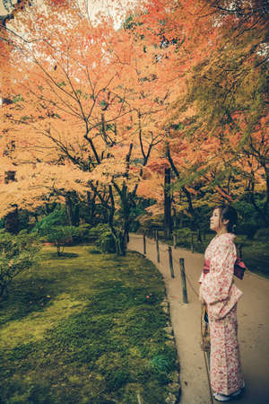 Cute Japanese girl is standing calmly in autumn wilderness landscape in stylish fashion color