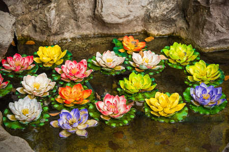 Colorful artificial lotus in the in the pond of the wishing well in Thailand photo