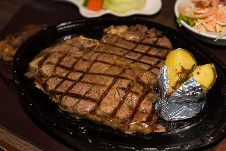 prime rib: Premium American prime rib steak on a metal plate ready to serve. The focus is shallow depth of field.