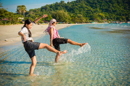 Two Asian Thai girls are kicking the sea along the beach coast of Rayong, Thailand photo