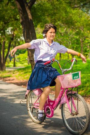 zapatos escolares: Tailandesa colegiala jugando arriesgada en una bicicleta, en la temporada de verano soleado.