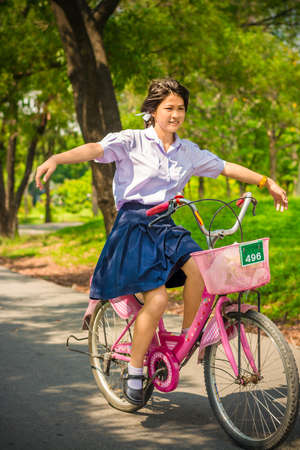 sexy school girl: Thai Schoolgirl playing risky on a bicycle , in the sunny summer season. Stock Photo