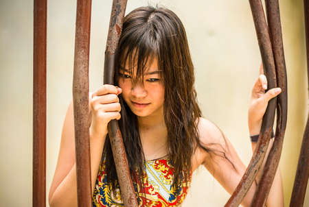prison break: Asian Thai girl is bending the prison bar with her power Stock Photo