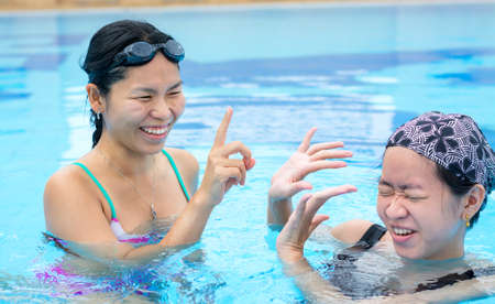 swimming costumes: Two Asian girls are flicking water to one another in the swimming pool with happy expression