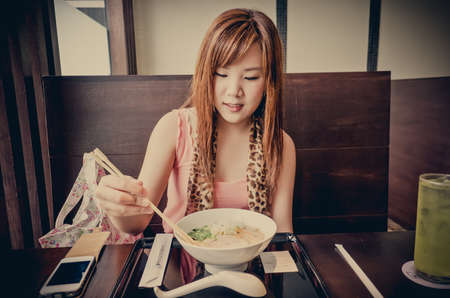 resturant: A cute Thai girl is preparing to eat Japanese Ramen in the resturant. This is urban life.