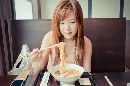 resturant: A cute Thai girl is eating a Japanese Ramen in the resturant in vintage color. This is urban life. Stock Photo