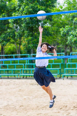 Cute Thai schoolgirl is playing beach volleyball in school uniform. Focus on the model face. photo