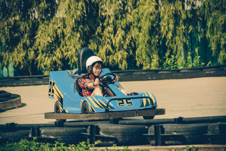 Cute Thai girl is driving Go-kart with speed in retro color photo