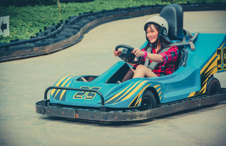 Cute Thai girl is driving Go-kart with speed in vintage color photo