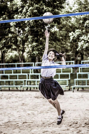 preteen  pure: Cute Thai schoolgirl is playing beach volleyball in school uniform in grunge style. Focus on the model face.