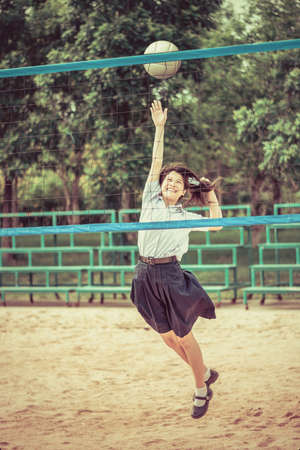 preteen  pure: Cute Thai schoolgirl is playing beach volleyball in school uniform in retro color. Focus on the model face.