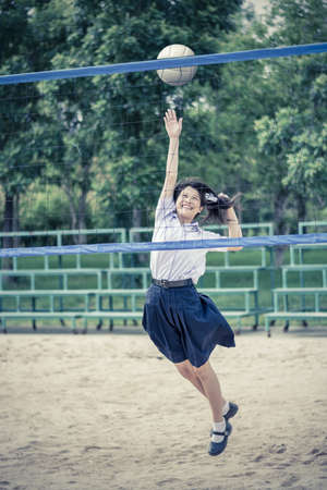 preteen  pure: Cute Thai schoolgirl is playing beach volleyball in school uniform in vintage color. Focus on the model face.