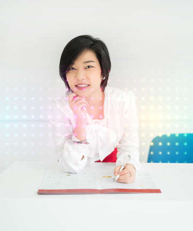 Cute Asian Thai businesswoman is working with her document file in office with colorful futuristic light effect, in the foreground photo