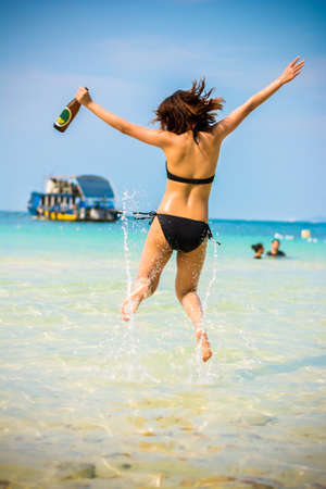 Sexy Asian Thai girl in bikini is jumping with joy on the seashore of Pattaya sea with alcohol bottle on her hand and water splashing for summer vacation concept in vintage color photo