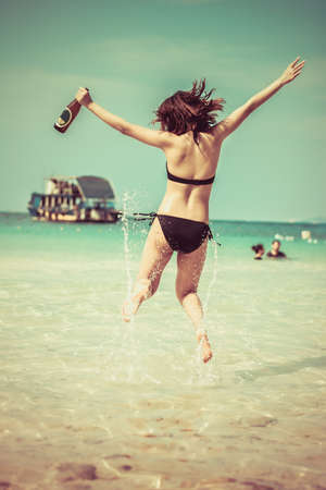 levitate: Sexy Asian Thai girl in bikini is jumping with joy on the seashore of Pattaya sea with alcohol bottle on her hand and water splashing for summer vacation concept in vintage color