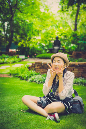 asian natural: Cute young Asian Thai girl with fashionalble clothes is sitting casually showing happy expression with her dslr camera in the wilderness garden with natural summer atmosphere in vintage color