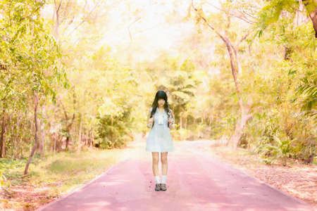 forest path: Watercolor illustration of a cute Asian Thai girl in vintage dress is standing on a romantic autumn seanson forest path alone