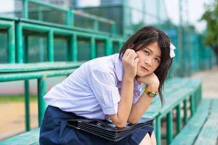 bashful: Shy Asian Thai schoolgirl student in high school uniform education fashion is sitting on a metal stand and showing facial bashful expression