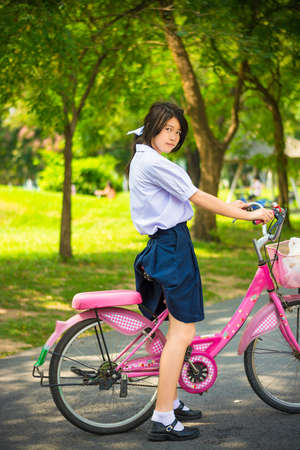 zapatos escolares: Estudiante tailandés asiática linda colegiala de manera uniforme de la escuela secundaria está de pie sobre su bicicleta rosada listo para ejercer en el parque soleado de verano con el medio ambiente verde Foto de archivo