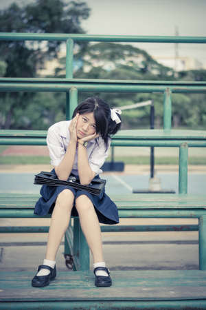 Asian Thai schoolgirl student in high school uniform education fashion is sitting on a metal stand and showing annoying sulk facial expression in vintage retro color. She kept something in mind and not in good mood.