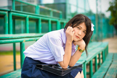 shy: Shy Asian Thai schoolgirl student in high school uniform education fashion is sitting on a metal stand and showing facial bashful expression