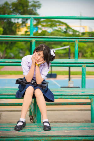 vestidos de epoca: Estudiante asiático colegiala tailandés en alta escuela de moda educación uniforme está sentado sobre un soporte de metal y que muestra molesto Sulk expresión facial. Ella mantuvo algo en mente y no en buen estado de ánimo. Foto de archivo