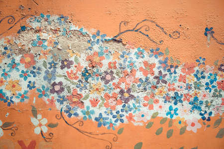 wall mural: Part of old flower flora mural painting pattern art on a messy crack wall texture background in vintage retro color
