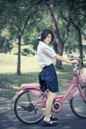 zapatos escolares: Cite Estudiante asiático colegiala tailandesa de manera uniforme de la escuela secundaria está de pie junto a su bicicleta rosa listo para ejercer en el soleado parque de verano con el entorno verde en el color de la vendimia. Foto de archivo