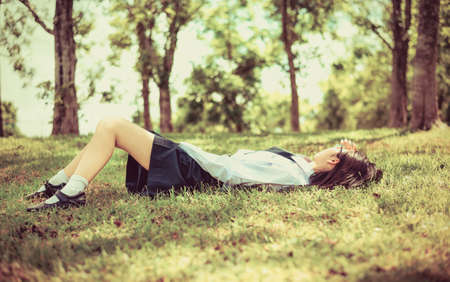 Asian Thai teenage female schoolgirl student in high school uniform with leather shoes lie down sleeping or relaxing on the green grass field wilderness park with summer natural sunlight in old vintage retro color Stock Photo