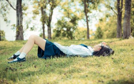 アジア タイ、睡眠やリラックス グリーンの横に高校制服革靴で 10 代女性女子高生生草の古いビンテージ レトロな色で夏自然太陽光でフィールド荒
