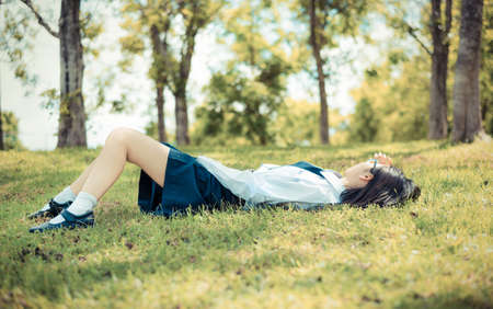 Asian Thai teenage female schoolgirl student in high school uniform with leather shoes lie down sleeping or relaxing on the green grass field wilderness park with summer natural sunlight in old vintage retro color 版權商用圖片