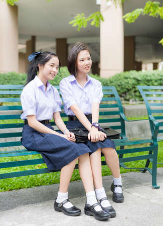 Cute Asian Thai high schoolgirls student couple in school uniform sit wih a happy smile face together on a bench