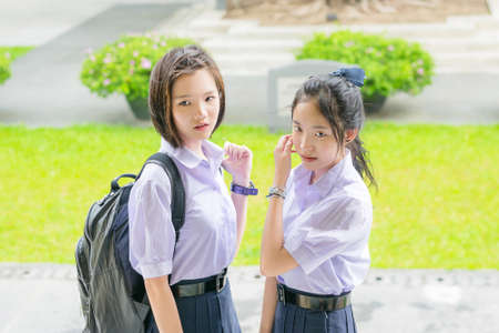 thai student: Cute Asian Thai high schoolgirls student couple in school uniform standing with her friend showing curious or watching face expression Stock Photo