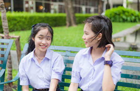 thai student: Cute Asian Thai high schoolgirls student couple in school uniform chatting with her friend showing happy smile face expression on a bench