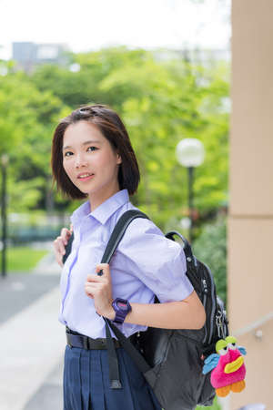 thai student: Cute Asian Thai high schoolgirl student with short hair in school uniform standing with happy smile face expression in nature green background Stock Photo