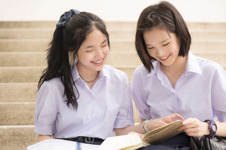 Cute Asian Thai high schoolgirls student couple in school uniform sit on the stairway discussing homework or exam with a happy smiling face together on a building stairs Stock Photo