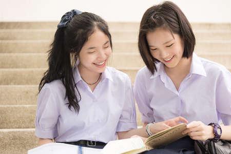 Mignon élevé écolières couple d'étudiants thaïlandais asiatique en uniforme scolaire assis sur l'escalier discuter des devoirs ou examen avec un visage souriant heureux ensemble sur un bâtiment escalier