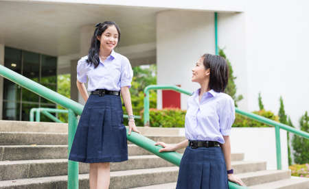 thai student: Cute Asian Thai high schoolgirls student couple in school uniform stand on the stairway making eye contact