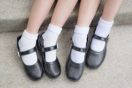 Asian Thai girls schoolgirl student feet with black leather shoes as a school uniform. It is teenage education fashion. Stock Photo
