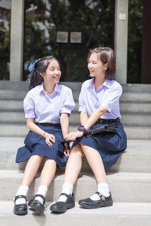 zapatos escolares: Asian Thai de escuelas secundarias estudiante linda pareja en uniforme escolar se sienta en la escalera charlando con una cara sonriente y riendo felices juntos en un edificio escaleras Foto de archivo