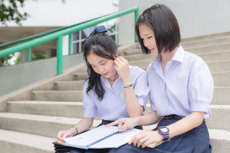 thai student: Cute Asian Thai high schoolgirls student couple in school uniform sit on the stairway discussing homework or exam with a happy smiling face together on a building stairs Stock Photo