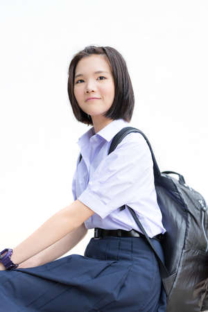 Cute Asian Thai high schoolgirl student in school uniform sitting with her backpack showing smiling happy facial expression in white isolated background