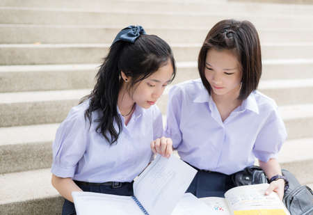 Cute Asian Thai high schoolgirls student couple in school uniform sit on the stairway discussing homework or exam together on a building stairs