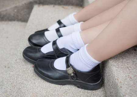 thai student: Side of Asian Thai girls schoolgirl student feet with black leather shoes as a school uniform. It is teenage education fashion. Stock Photo