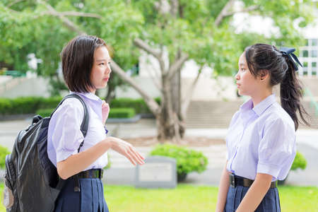 thai student: Cute Asian Thai high schoolgirls student couple in school uniform talking and discussing with her friend face expression in green background