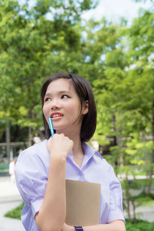 thai student: Cute Asian Thai high schoolgirls student with short hair in school uniform standing with her school staionary pen and notebook with happy smile face expression in nature green background