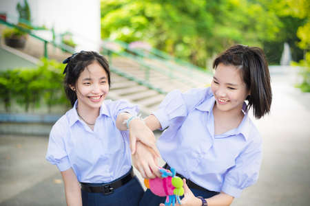 chasing: Cute Asian Thai high schoolgirls student couple in school uniform are having fun playing chasing and catching a doll with her student friend in a happy smile face expression Stock Photo