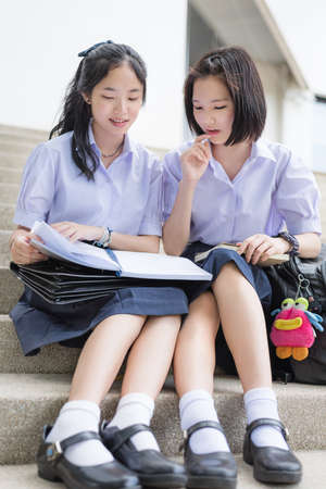 thai student: Cute Asian Thai high schoolgirls student couple in school uniform sit on the stairway discussing homework or exam with a happy smiling face together on a building stairs. Focus mainly on the book.