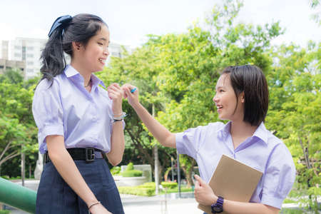 teasing: Cute Asian Thai high schoolgirls student couple in school uniform talking and teasing with her friend in happy face expression in green background Stock Photo